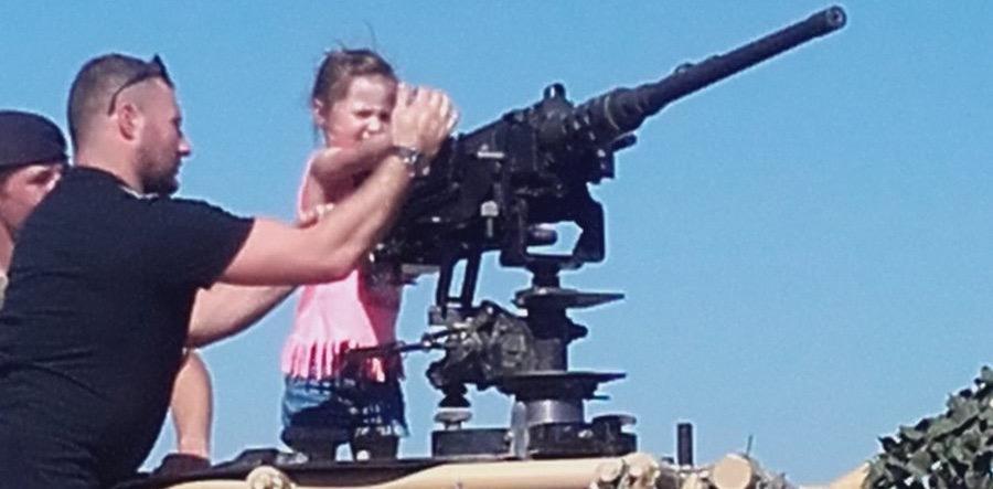 A small child handling a machine gun on Armed Forces Day 2018, Llandudno