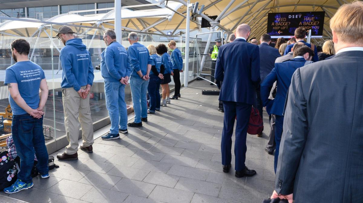 Members of Veterans for Peace turn their backs as arms dealers and their customers arrive for DSEI 2019