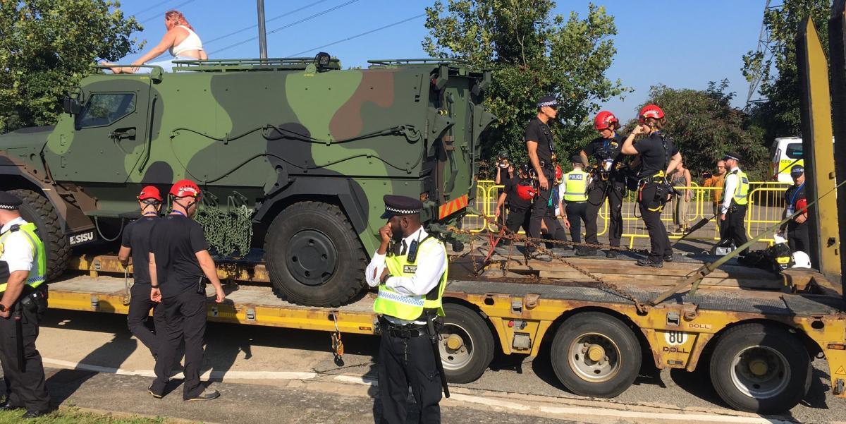 Protester climbing on armoured vehicle on the way into DSEI