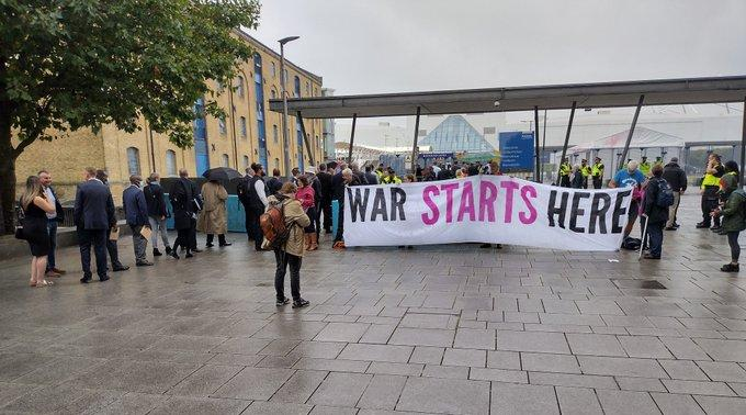 """A banner reading """"War starts here"""" faces arms dealers queueing up at DSEI"""