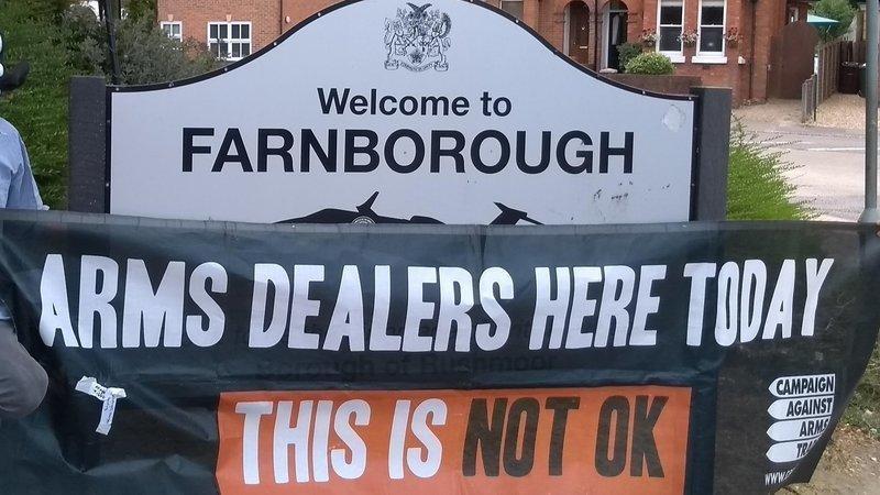 Anti-arms trade banner next to sign for Farnborough