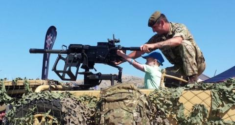 A soldier inviting a small child to handle a gun at the Armed Forces Day National Event in Llandudno, 2018