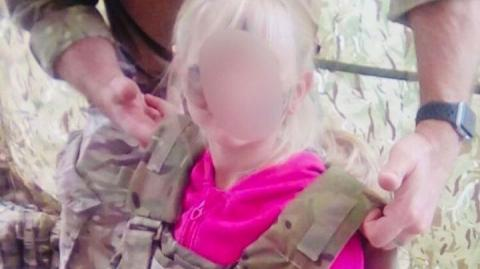 Small child with military body armour being placed on her