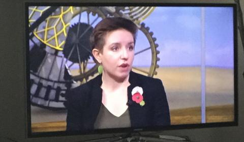 Carla Denyer wearing a white poppy and a red poppy together