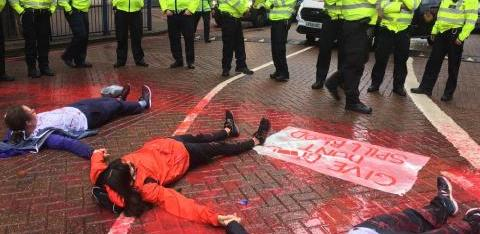 Three people lie glued together in the road with police in front of them
