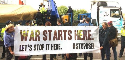"""Protest at DSEI with a banner reading """"War starts here"""""""