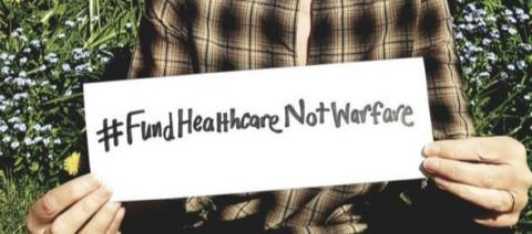 Poster reading, 'Fund Healthcare Not Warfare'