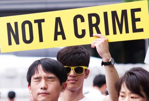 "South Korean campaigners hold a sign reading ""Not a crime"""
