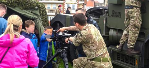 Members of the Royal Air Force showing weapons to small children